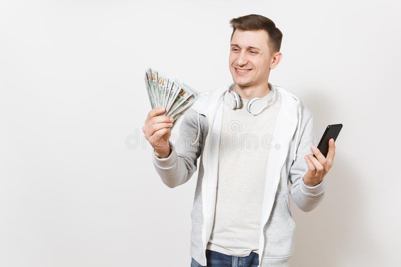Young handsome smiling man in t-shirt and light sweatshirt with headphones around neck holds bundle of dollars, cash royalty free stock photos