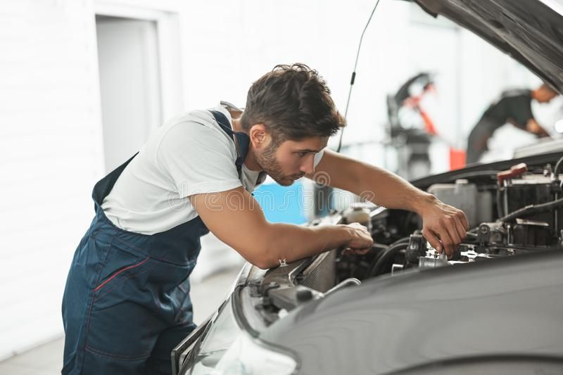Young handsome smiling mechanic in uniform fixing motor in car bonnet working in service department.  royalty free stock photography