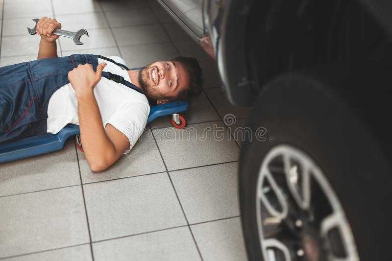 Young handsome smiling mechanic in uniform working in car service department fixing vehicle chassis with help of spanner. Showing like sign royalty free stock image