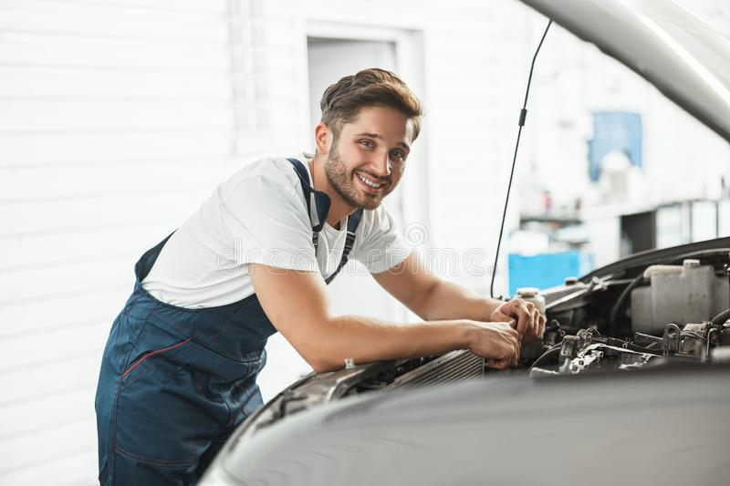 Young handsome smiling mechanic wearing uniform fixing motor in car bonnet working in service department.  stock photo