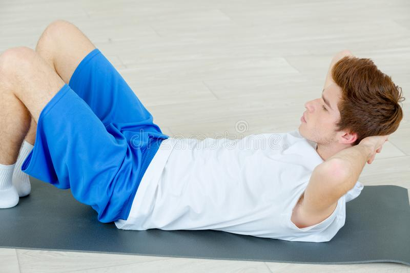 Young handsome sportsman doing exercises indoor royalty free stock images