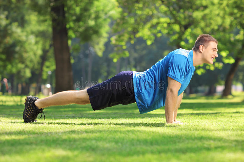 Young Handsome Sportsman Exercising In A Park Stock Photos