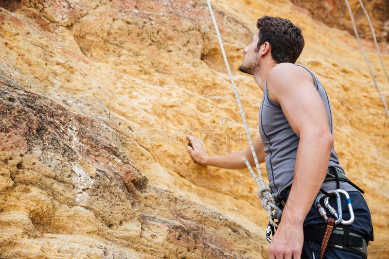 Young handsome sportsman getting ready to climb a cliff. Young handsome sportsman getting ready to climb a rock cliff stock photos