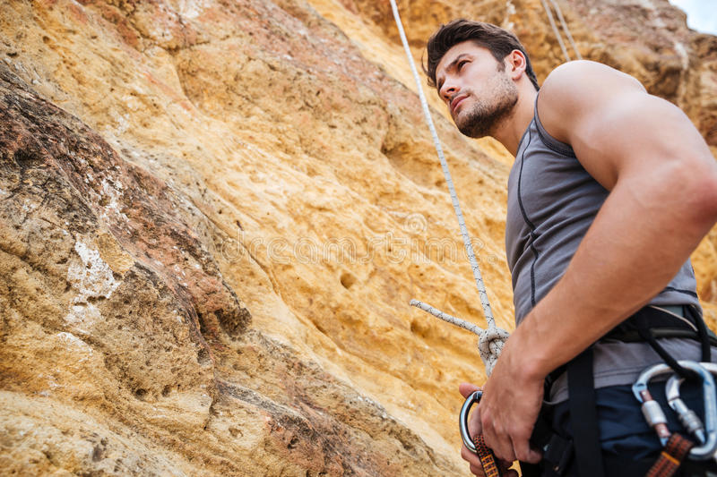 Young handsome sportsman getting ready to climb a cliff. Young handsome sportsman getting ready to climb a rock cliff stock images