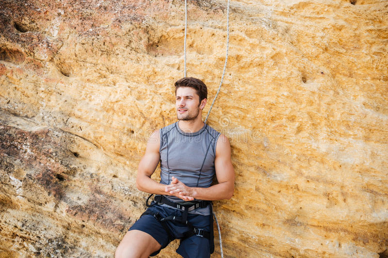 Young handsome sportsman getting ready to climb a cliff. Young handsome sportsman getting ready to climb a rock cliff royalty free stock photography