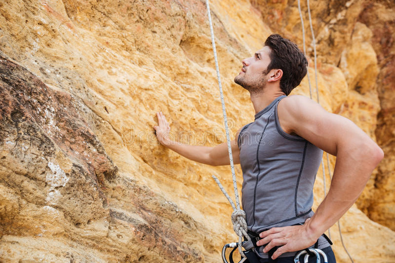 Young handsome sportsman getting ready to climb a cliff. Young handsome sportsman getting ready to climb up a rock cliff royalty free stock image
