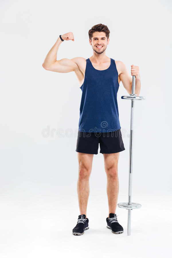 Young handsome sportsman holding barbell and showing biceps. Young handsome smiling sportsman holding barbell and showing biceps isolated on a gray background royalty free stock image