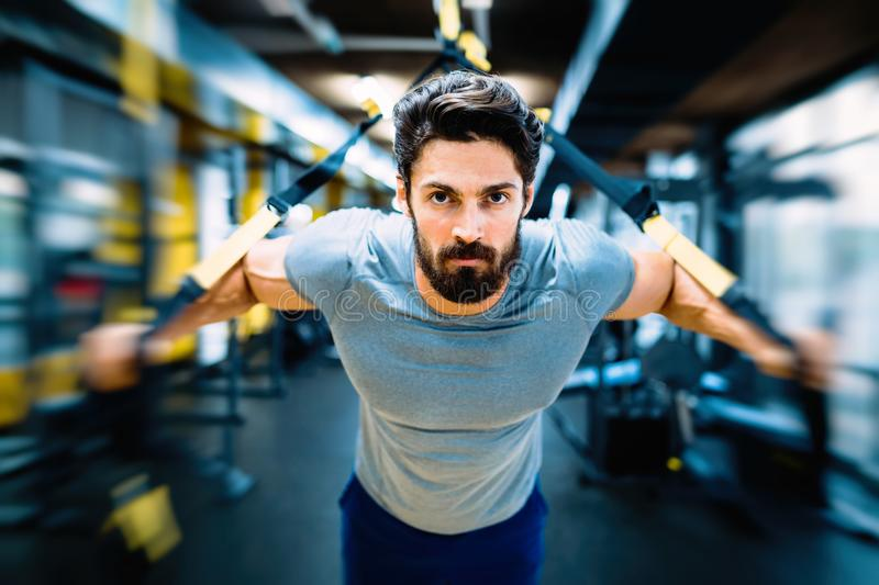 Young handsome man doing exercises in gym royalty free stock photos