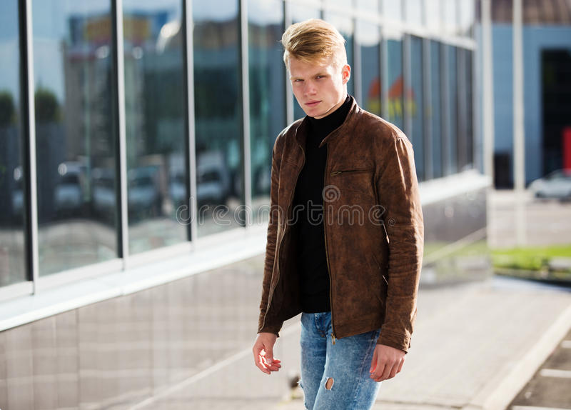 Young handsome stylish man in brown jacket in autumn time outdoor in casual style.  stock images