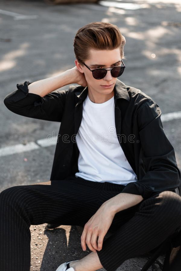 Young handsome stylish man in elegant clothes in trendy sunglasses with a hairstyle sitting on the asphalt. In a city on a sunny summer day. Modern urban guy royalty free stock photos