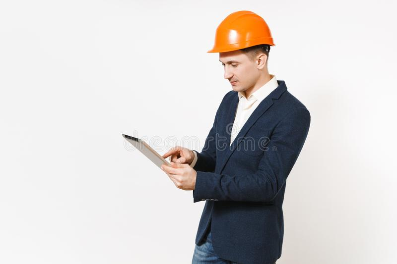 Young handsome successful businessman in dark suit, protective construction orange helmet using tablet pc computer stock photos