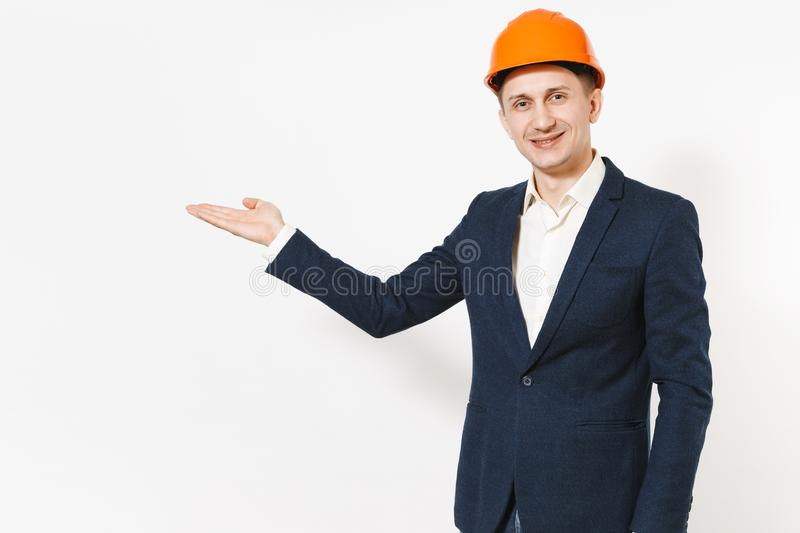Young handsome successful businessman in dark suit, protective hardhat pointing hand aside on copy space isolated on royalty free stock images