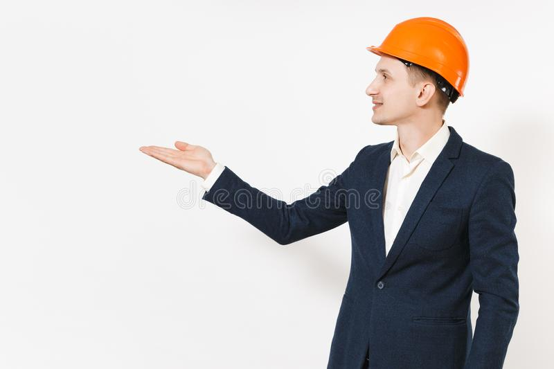 Young handsome successful businessman in dark suit, protective hardhat pointing hand aside on copy space isolated on stock image