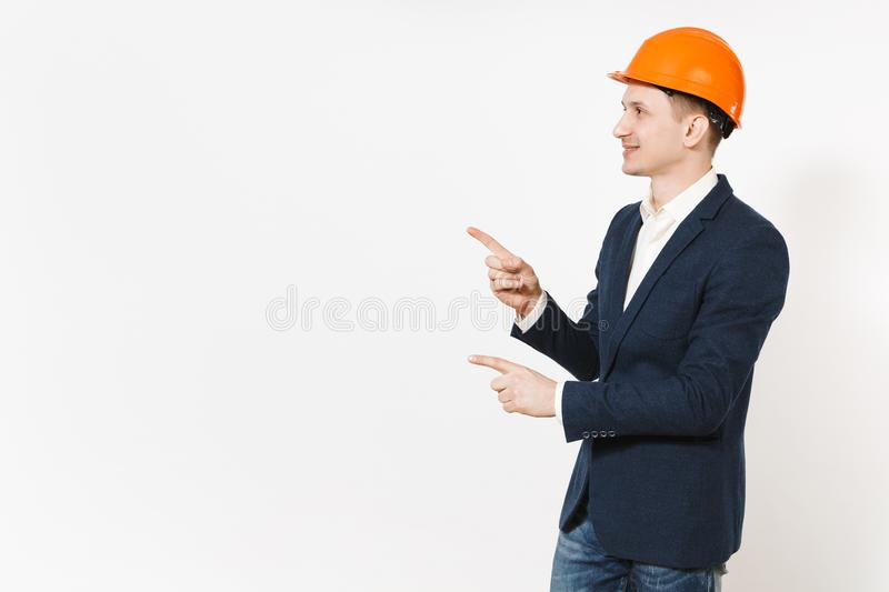Young handsome successful businessman in dark suit, protective hardhat pointing index fingers aside on copy space royalty free stock images