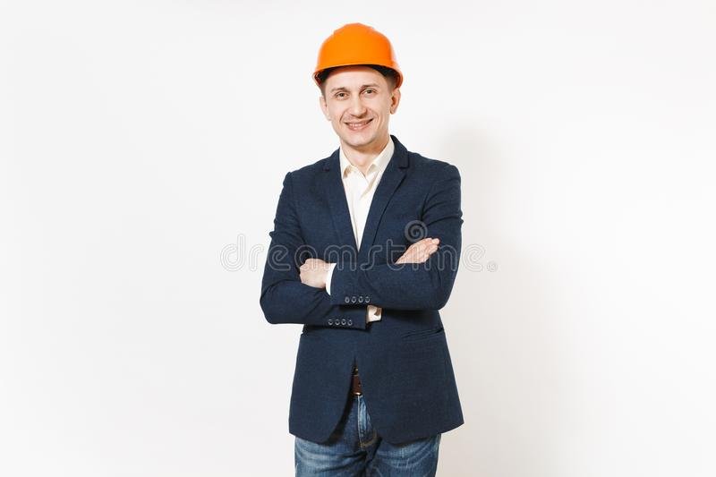 Young handsome successful smiling businessman in dark suit, protective construction helmet holding hands folded isolated stock images
