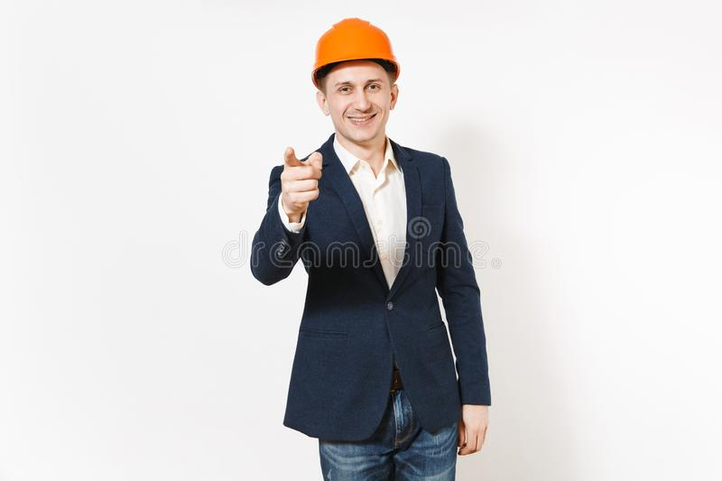 Young handsome successful smiling businessman in dark suit, protective hardhat pointing index finger on camera isolated royalty free stock image