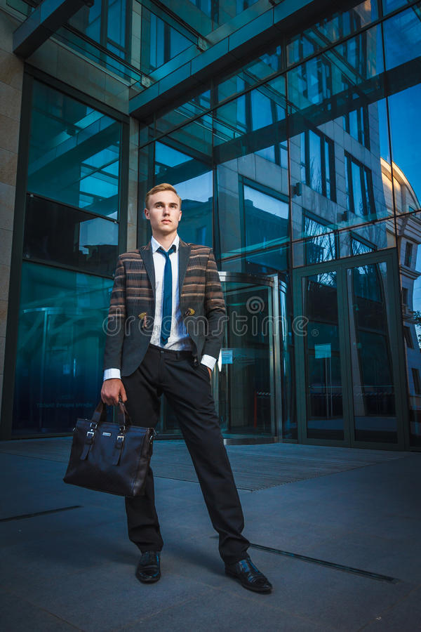 Young handsome successful stylish businessman standing near modern office. Building. Concept: victory royalty free stock photography