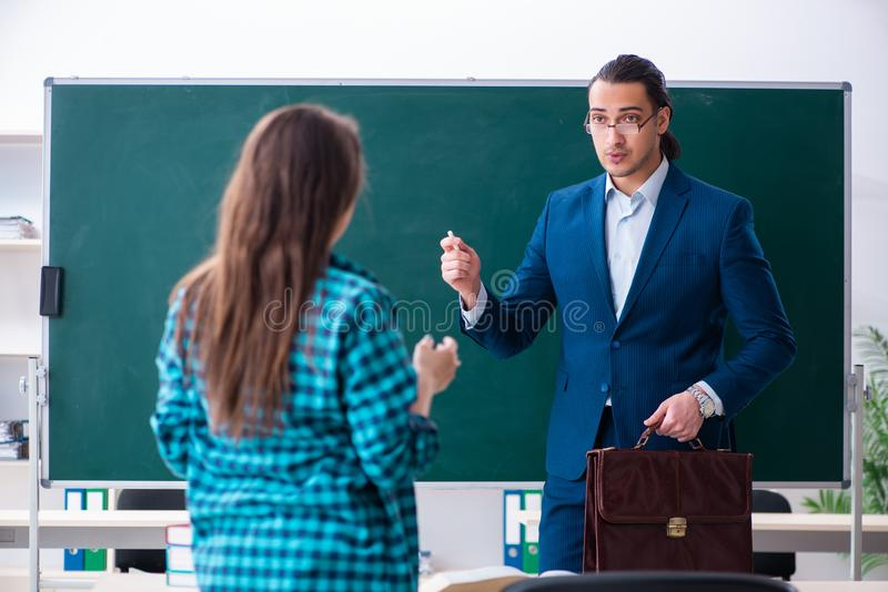 The young handsome teacher and female student in the classroom stock photography