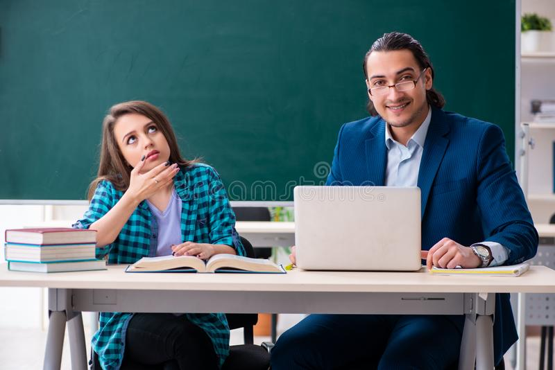 Young handsome teacher and female student in the classroom stock images