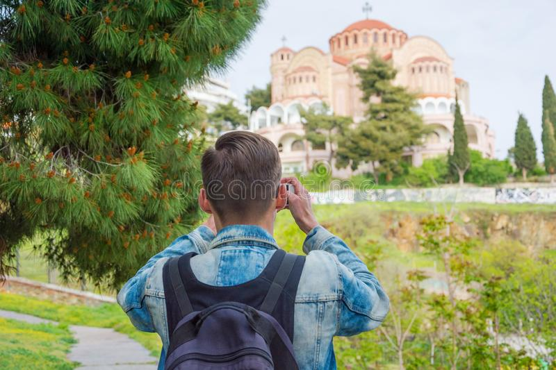 Young handsome tourist, with backpack taking pictures on a smartphone of the Church St. Paul in the in the Ano Poli in royalty free stock photos