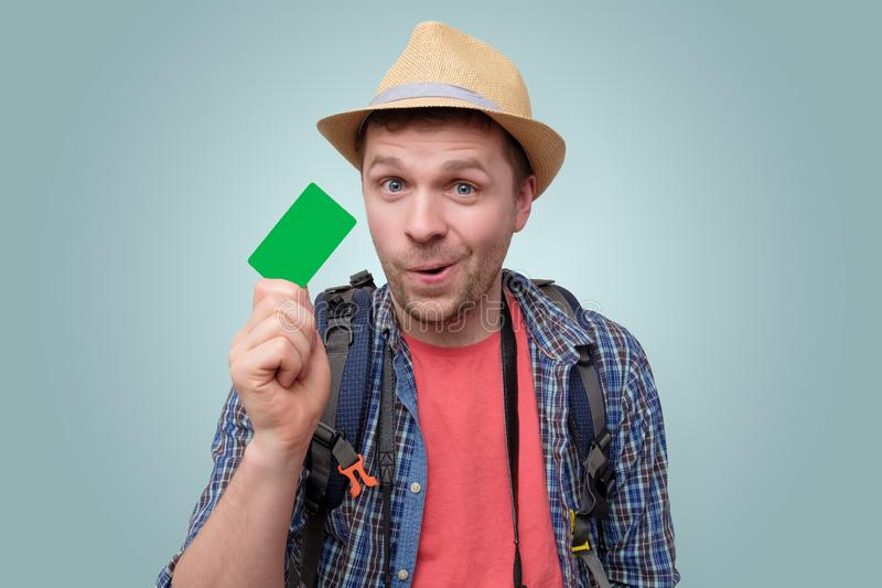 Young handsome tourist man holds green credit card. Having a credit card on vacation stock image