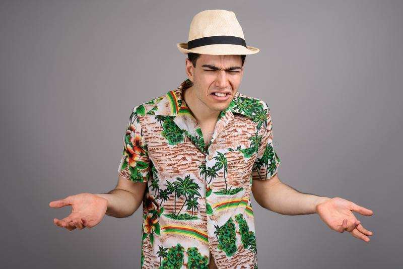 Young handsome tourist man ready for vacation against gray backg. Studio shot of young handsome tourist man wearing Hawaiian shirt and hat ready for vacation stock image