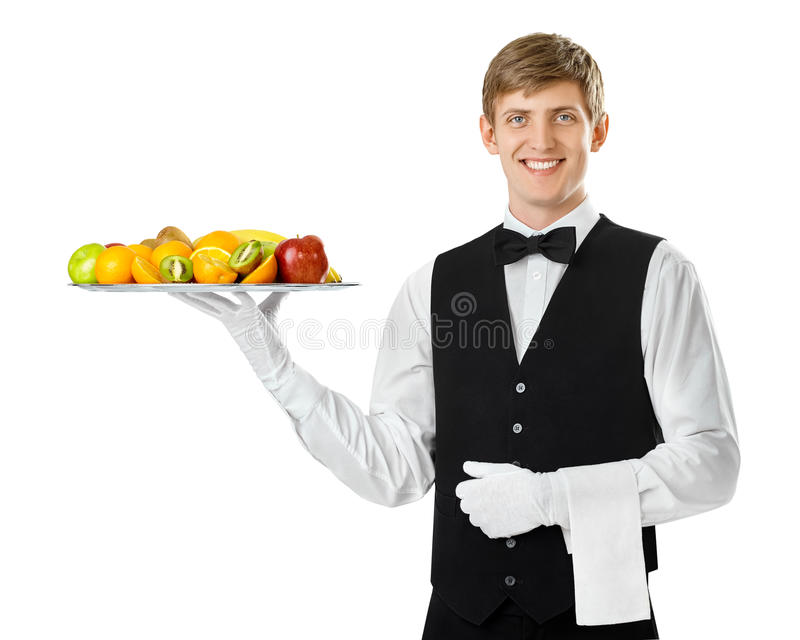 Young handsome waiter holding big tray full of fresh fruits royalty free stock image