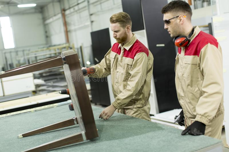 Young workers works in a factory for the production of furniture royalty free stock photo