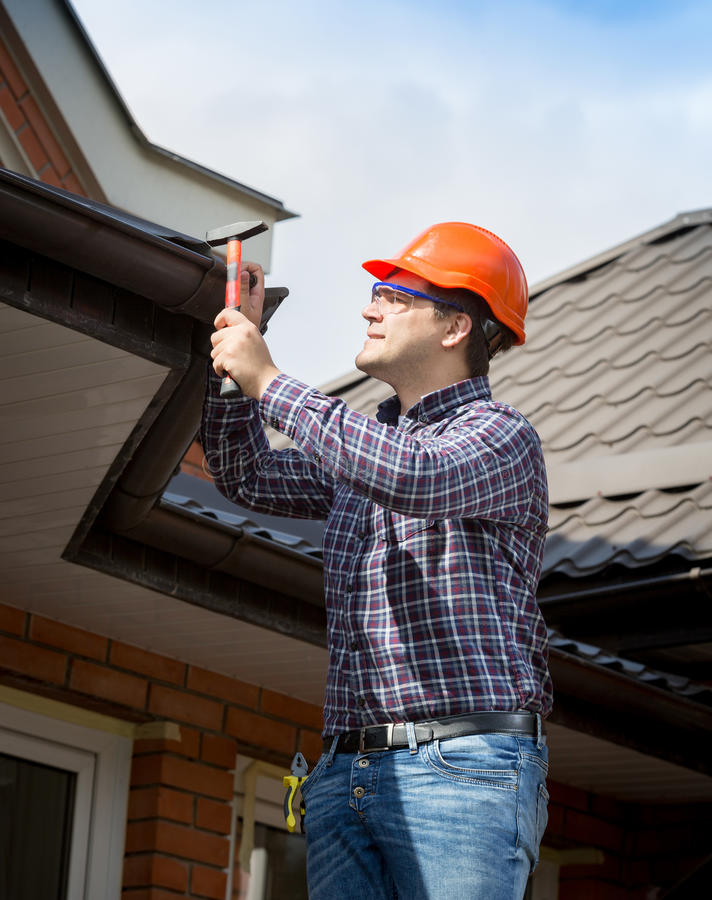 Young handyman repairing house roof with nails and hammer stock photography
