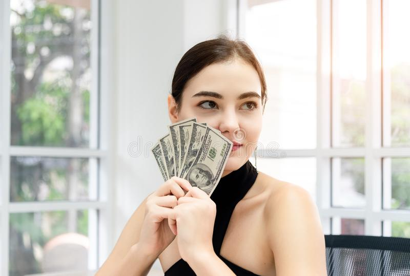 Young happiness pretty caucasian woman holding dollars bank and purchasing online with laptop computer. Online shopping payment , stock photography