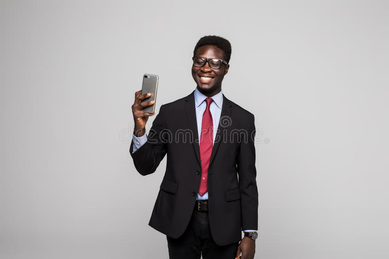 Young happy African businessman taking selfie on grey background stock photo