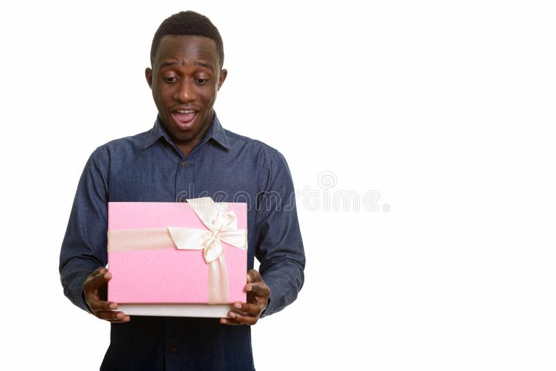 Young happy African man smiling and opening gift box. Isolated against white background royalty free stock image