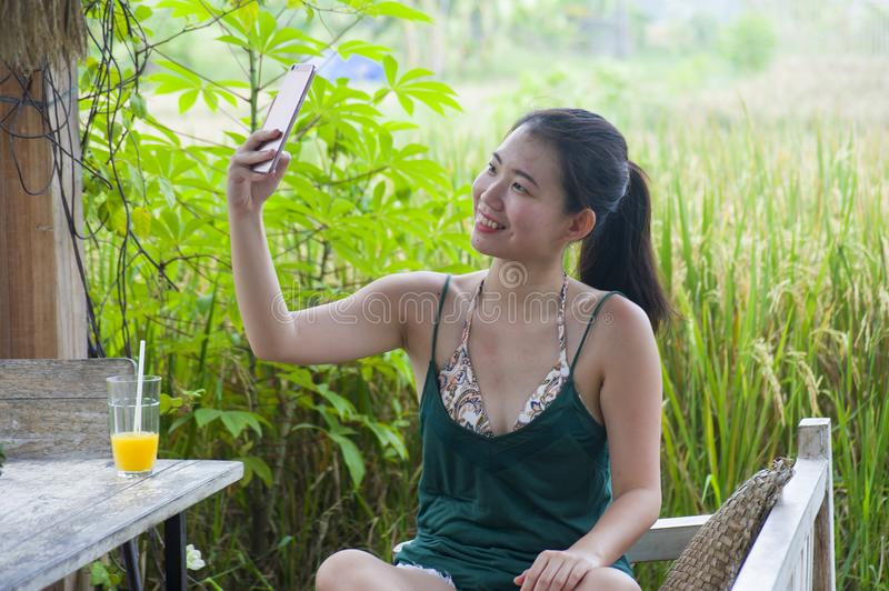 Happy Asian Chinese woman on her 20s or 30s smiling having fun taking selfie pic with mobile phone at rice field cafe having orang. Young happy Asian Chinese stock images