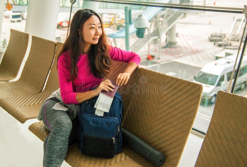 Young happy asian girl waiting for departure in international airport. royalty free stock photography
