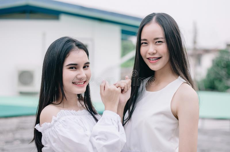 Young happy Asian girls best friends smile standing together and finger holding together,concept friendship sign stock image