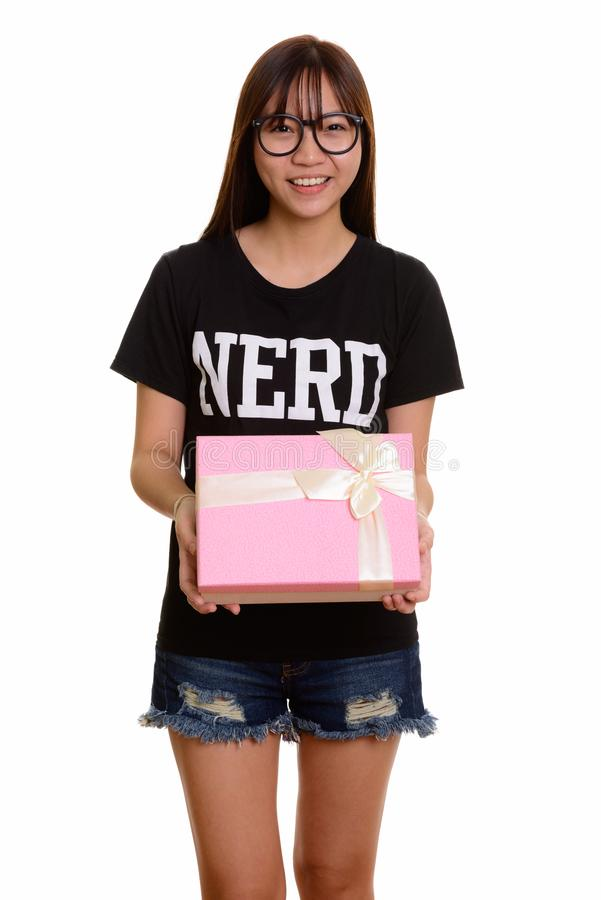 Young happy Asian nerd teenage girl smiling holding gift box. Isolated against white background royalty free stock images