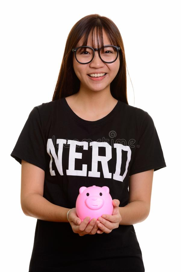 Young happy Asian nerd teenage girl smiling and holding piggy ba. Nk royalty free stock photo