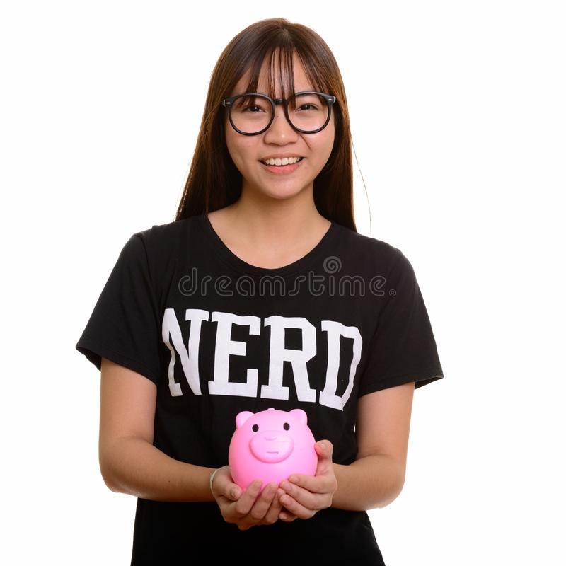 Young happy Asian nerd teenage girl smiling and holding piggy ba. Nk royalty free stock image