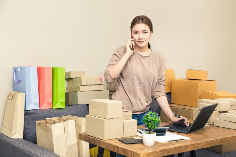 Young happy asian online seller, business woman, in her home talking to her customer on her phone while looking at camera stock images