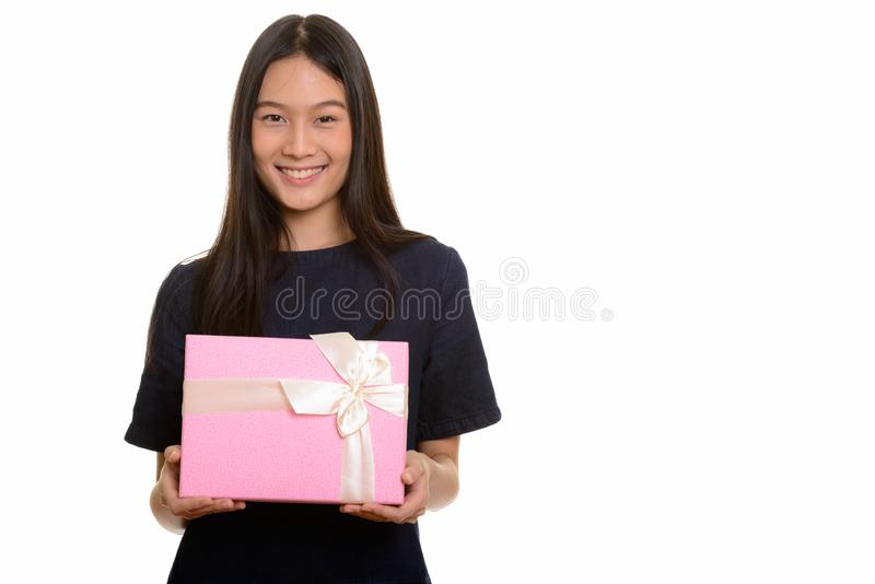 Young happy Asian teenage girl smiling and holding gift box royalty free stock photo