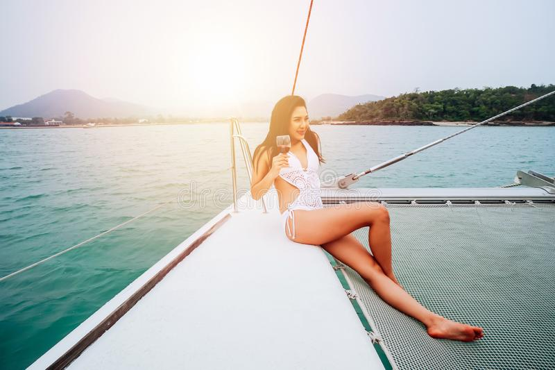 Young happy Asian woman enjoy and hold a wineglass sitting on deck of sailing yacht boat in bikini stock photo