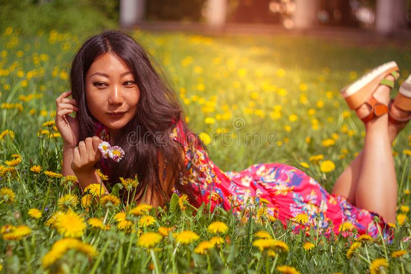 Young happy asian woman in the field with dandelions in the meadow a sunny day. Young happy asian woman in the green field with dandelions in the meadow a sunny royalty free stock photography