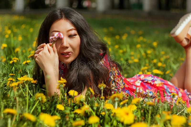 Young happy asian woman in the field with dandelions in the meadow a sunny day. Young happy asian woman in the green field with dandelions in the meadow a sunny stock photography