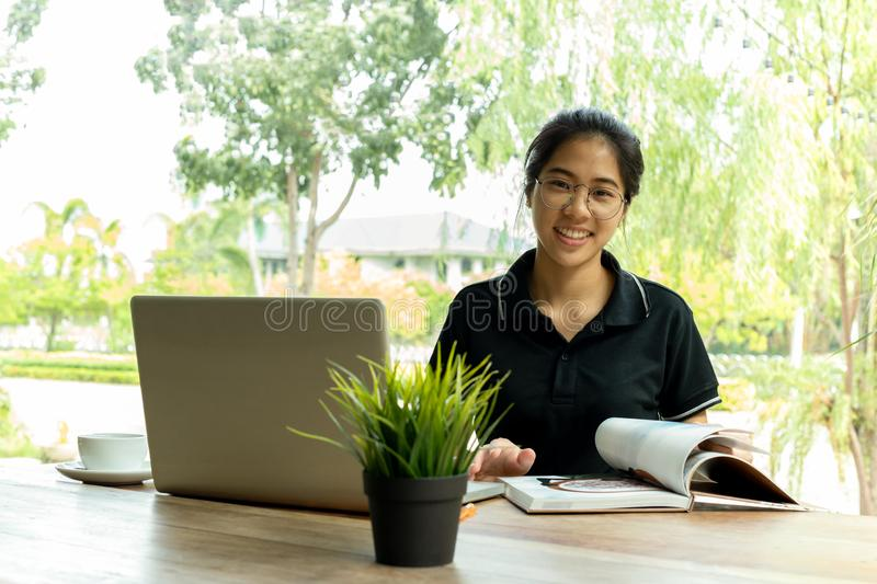 Asian woman with glasses smiling and open a book with laptop on table in cafe. stock photos