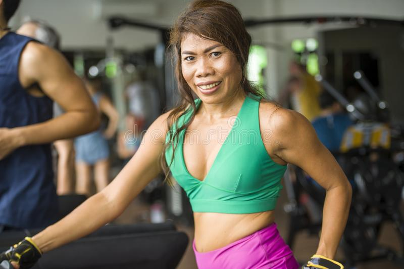 Young happy and athletic Asian Indonesian sport woman running on treadmill at gym fitness club training hard jogging workout royalty free stock images