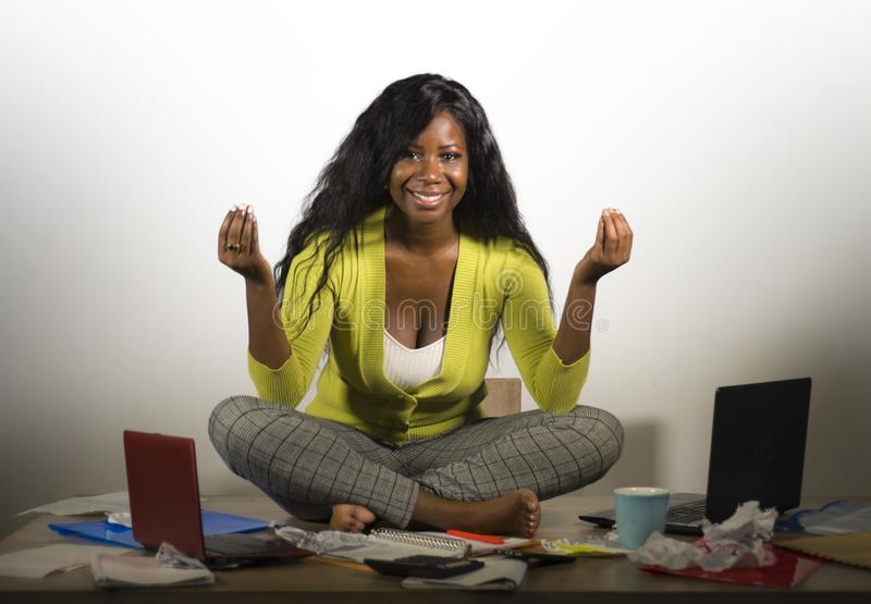 Young happy and attractive African American business woman doing yoga sitting at office messy desk full of paperwork smiling relax stock image