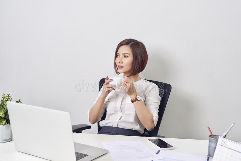 Young happy and attractive asian business woman working at office computer desk smiling drinking cup of coffee relaxed and royalty free stock photos