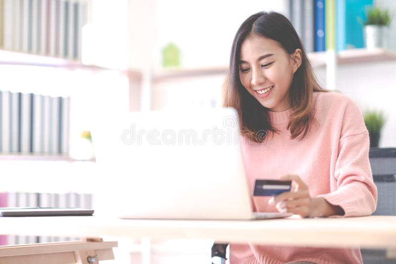 Young happy attractive asian female student, business owner, entrepreneur or freelancer smiling and sitting at home office behind stock photography
