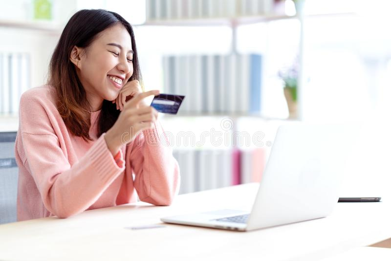 Young happy attractive asian female student, business owner, entrepreneur or freelancer smiling and sitting at home office behind stock image