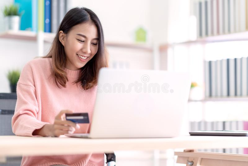 Young happy attractive asian female student, business owner, entrepreneur or freelancer smiling and sitting at home office behind royalty free stock photo